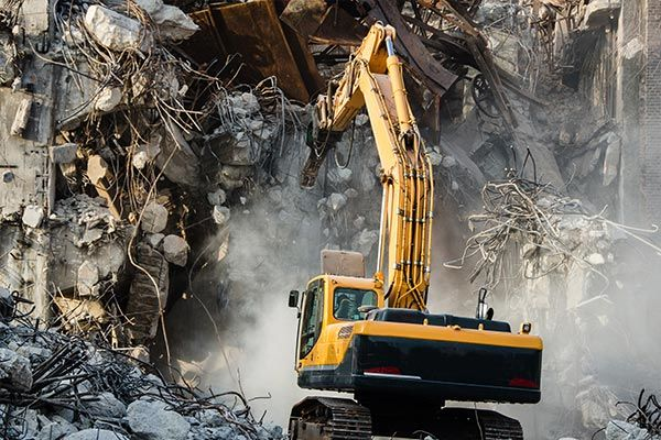 Demolition service equipment being used to demo a building that is falling apart